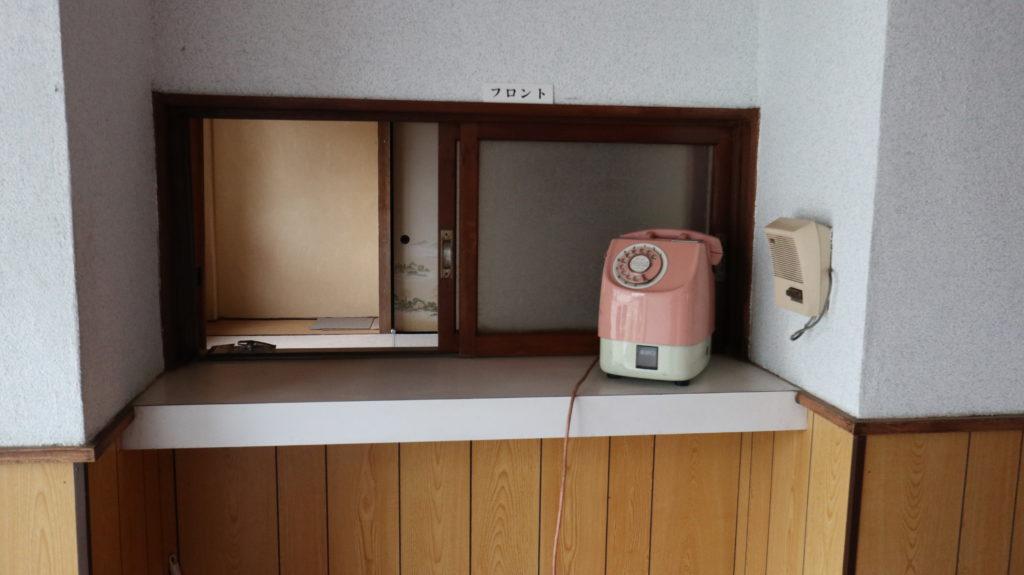 昭和のビジネスホテルスタジオフロントにピンクの公衆電話